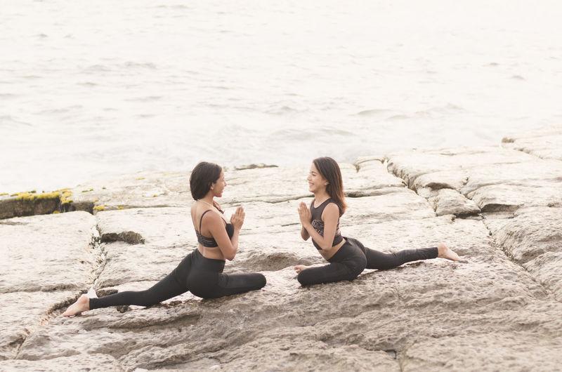 Women doing yoga on rocks