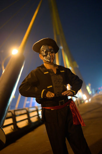 Portrait of young man wearing pirate costume standing on bridge at night