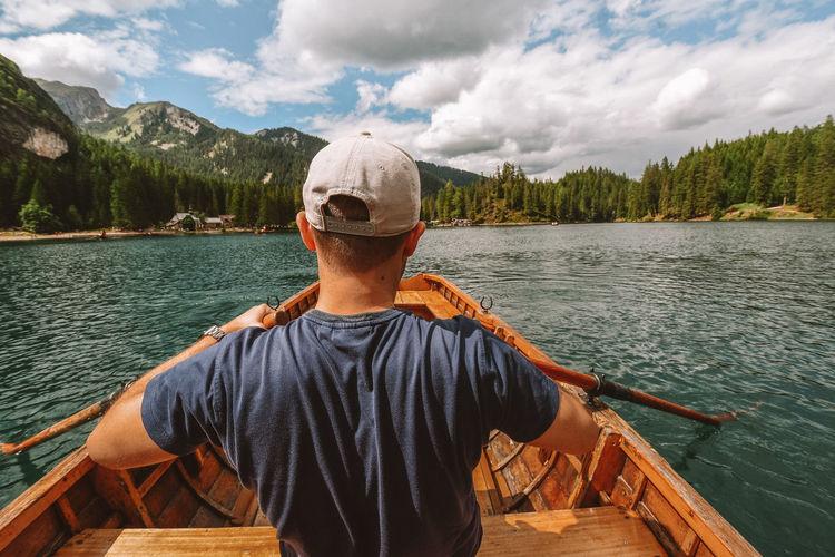 Rear view of man rowing on boat at lake