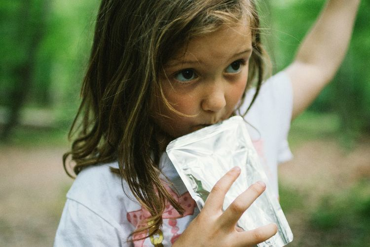 Close-Up Of Girl Drinking Juice While Standing On Field
