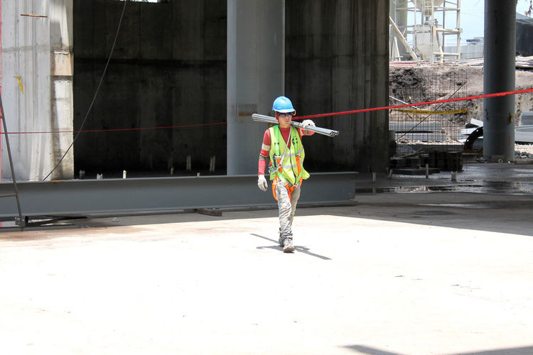Man carrying pipes on shoulder at construction site on sunny day