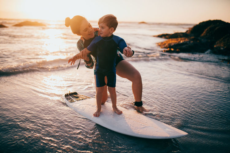 Sea Water Men Child Males  Childhood Boys Leisure Activity Two People Togetherness Real People Full Length Beach Family Sky Lifestyles Land Sunset Nature Son Positive Emotion Horizon Over Water Outdoors Surfing Learning