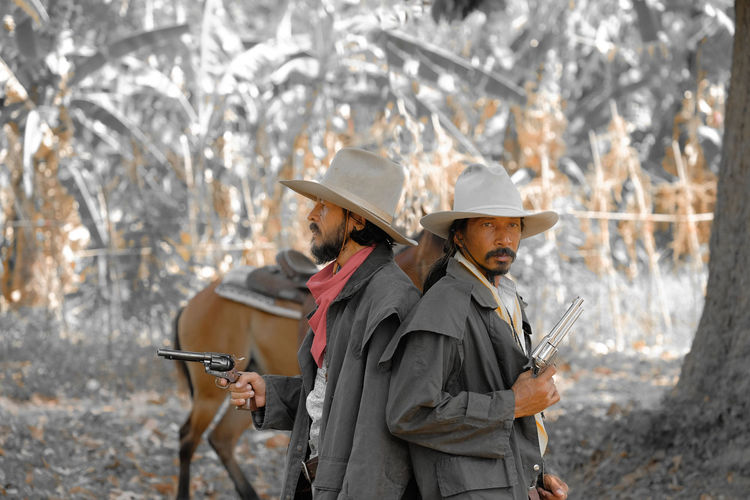 Male friends wearing hats holding guns in forest