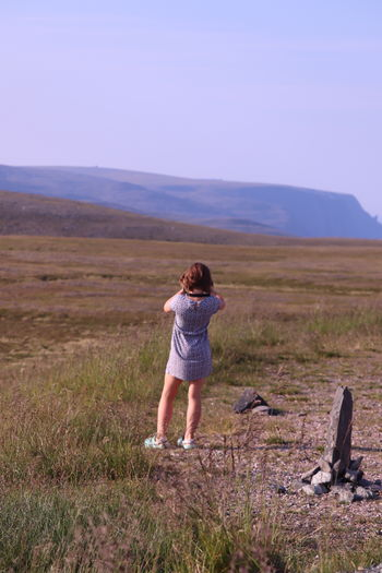 Rear view of girl standing on grassy field against blue sky