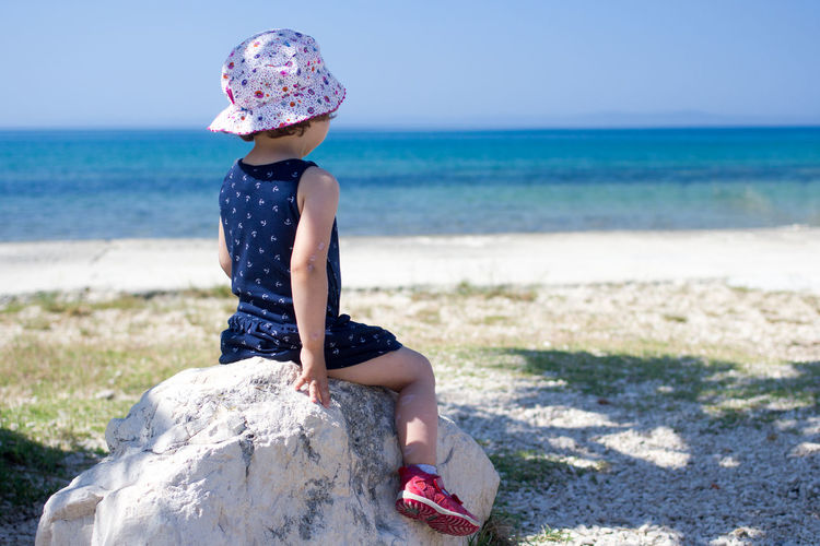 Rear view of girl sitting on rock at beach