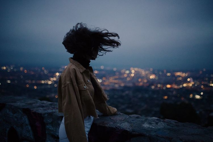 Side view of woman standing by retaining wall against sky at dusk