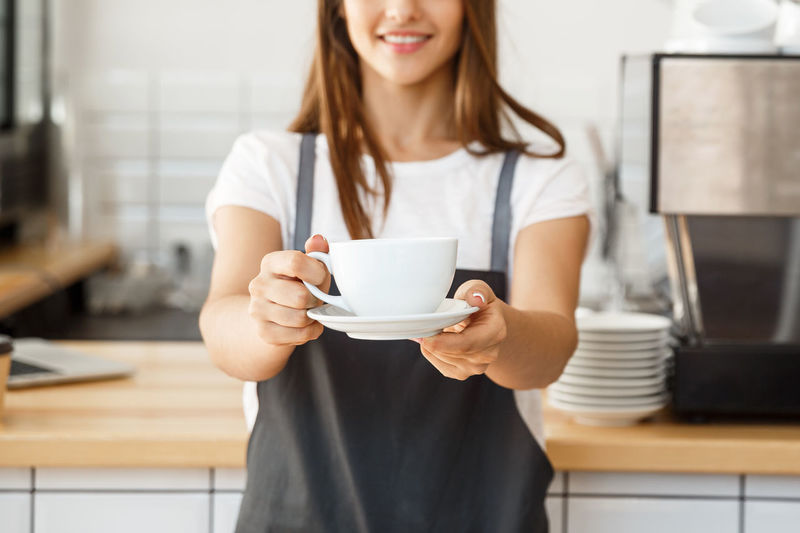 Midsection of barista holding coffee cup