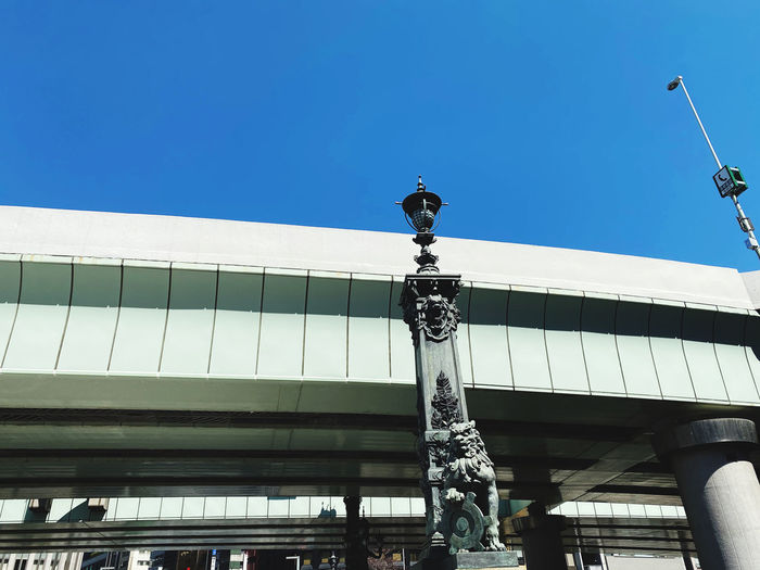 Low angle view of statue of building against blue sky
