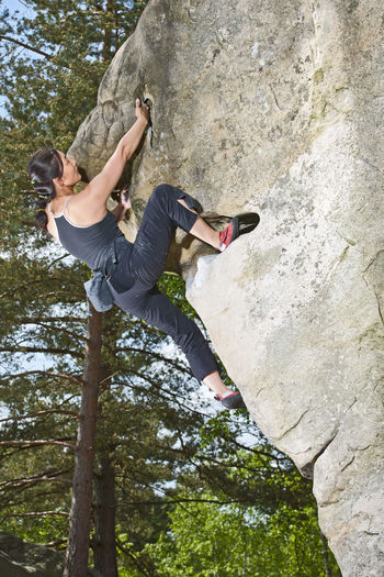 Low angle view of man climbing on rock