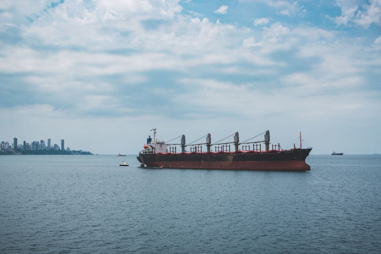 Ship on sea against cloudy sky