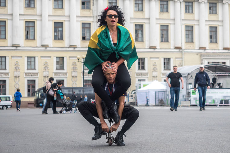 Elias de Souza Aguiar, brasilian football fan, on giant tandem in Saint-Petersburg, Russia, during FIFA world Cup 2018. Cycle Adult Architecture Bike Brasil Building Exterior Built Structure Casual Clothing City Day Fan Fifa2018 Front View Full Length Group Of People Incidental People Leisure Activity Lifestyles Men People Real People Small Bike Sport Women Young Adult