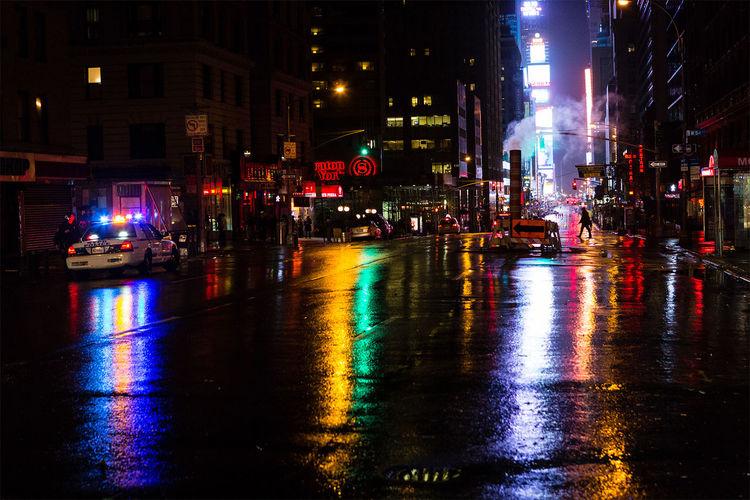 Rainy street in New York Night Illuminated Architecture Built Structure Building Exterior City Reflection Street Transportation Water Car City Life Wet Road City Street Land Vehicle Multi Colored Outdoors Manhattan Manhattan, New York City New York City