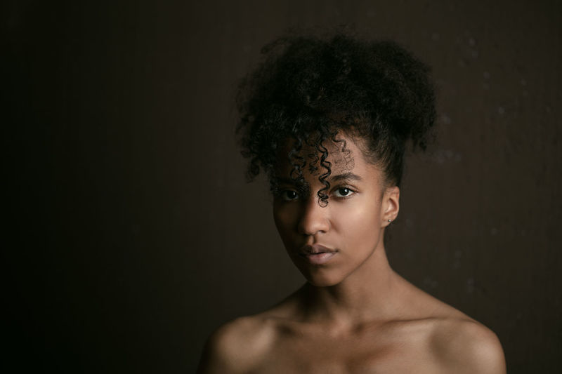 Portrait of shirtless young woman against black background