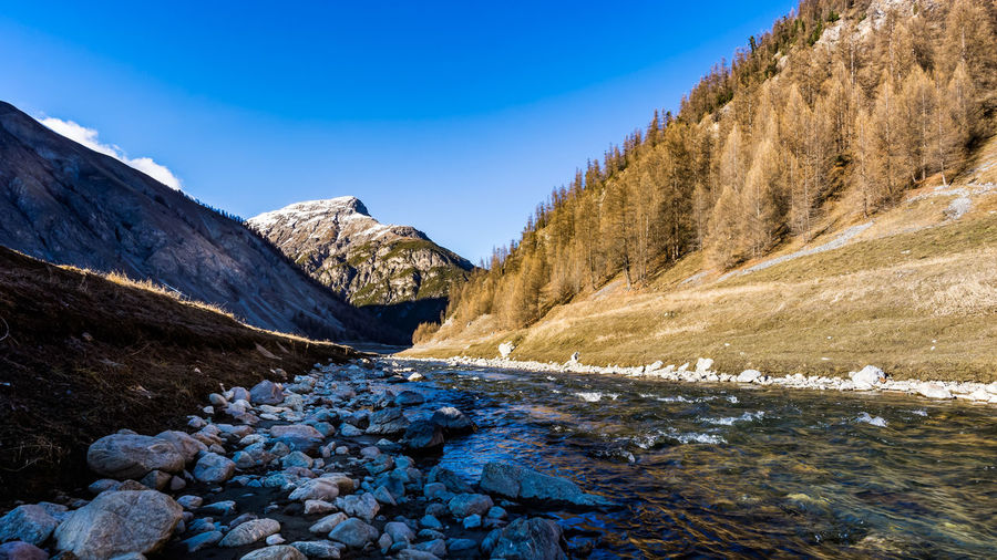 Scenic view of stream amidst snowcapped mountains against blue sky