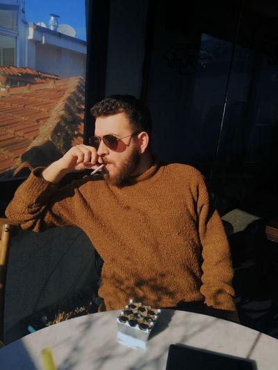 Man smoking cigarette at home
