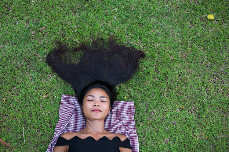 Directly Above Shot Of Woman Relaxing On Grassy Field