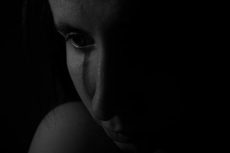 Close-Up Of Sad Woman Crying In Darkroom