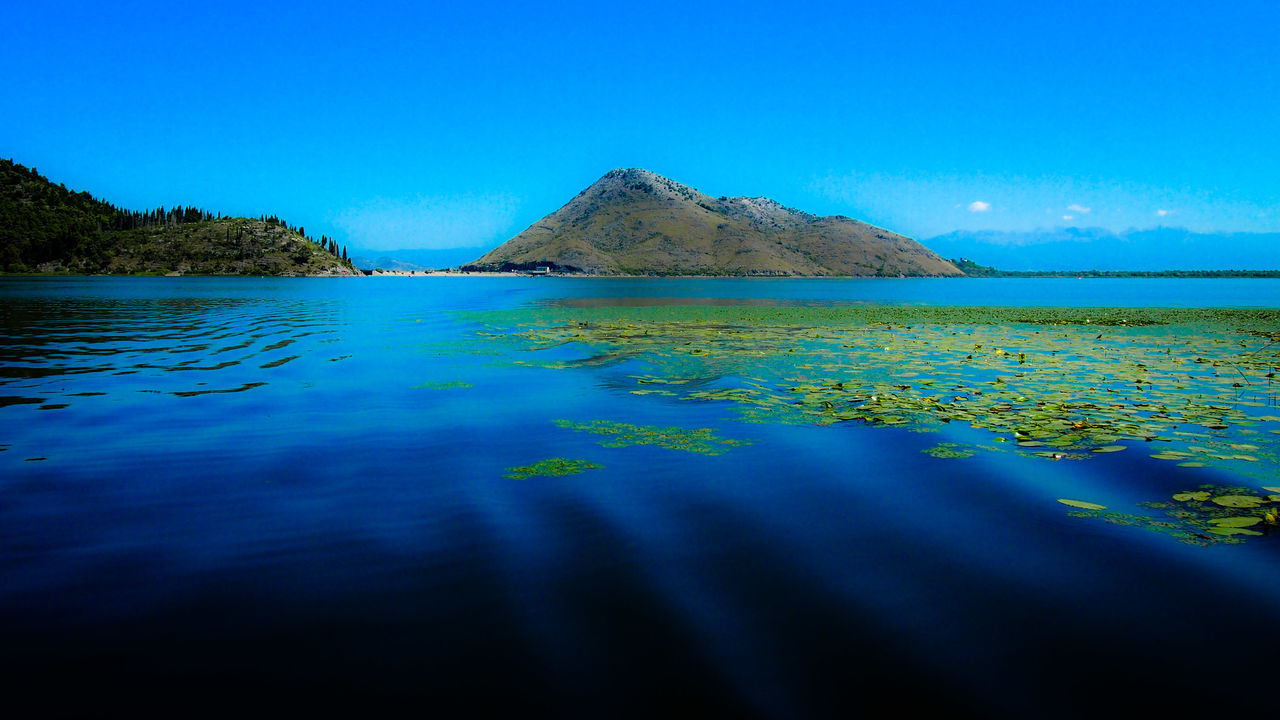 blue, scenics, tranquility, water, tranquil scene, beauty in nature, nature, no people, outdoors, day, rippled, waterfront, mountain, clear sky, sea, sky, tree