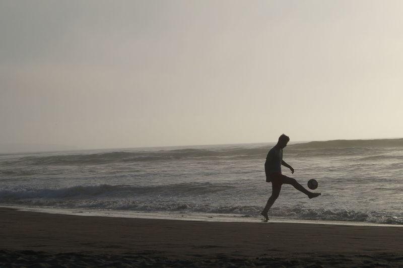 Man on beach against clear sky during sunset