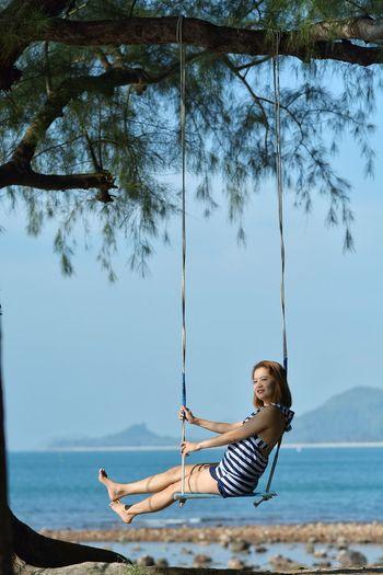 Full length of carefree woman swinging at beach