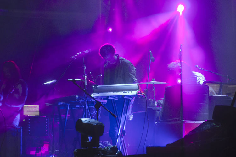 Low angle view of man playing piano on stage in music concert