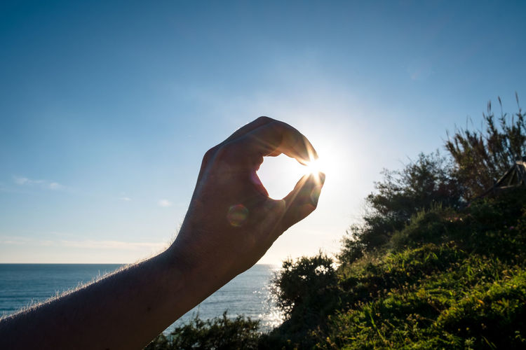 Optical illusion of cropped hand by sea holding sun in sky