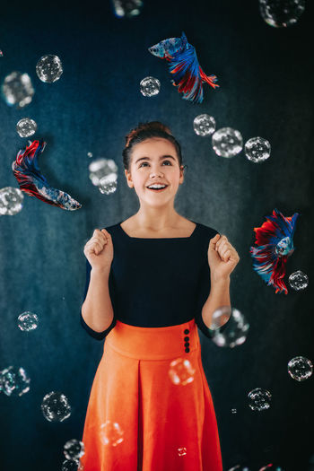 Digital composite image of smiling girl with fishes and bubbles against wall