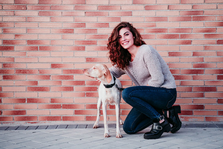 Young woman with dog on the brick wall