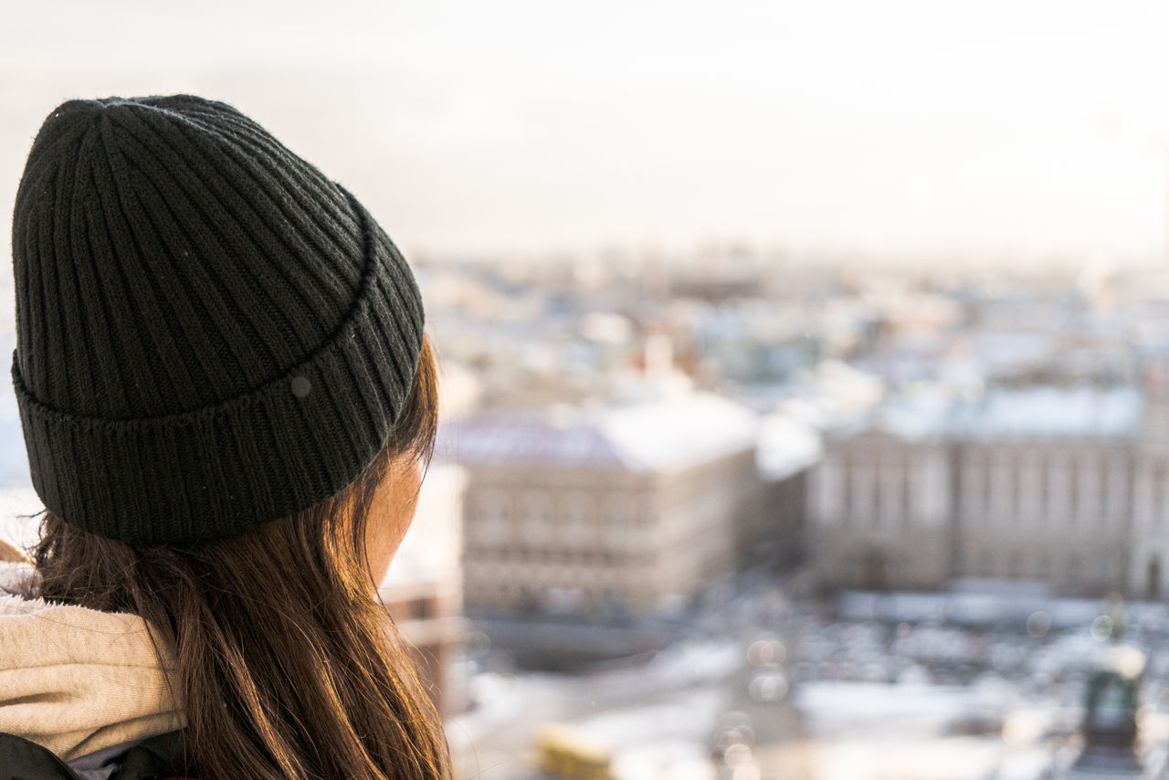 headshot, one person, architecture, built structure, rear view, portrait, building exterior, city, real people, hair, hairstyle, lifestyles, adult, leisure activity, women, focus on foreground, long hair, hat, clothing, cityscape, warm clothing, looking at view, outdoors