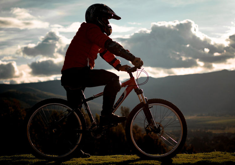 Man riding bicycle on field against sky during sunset