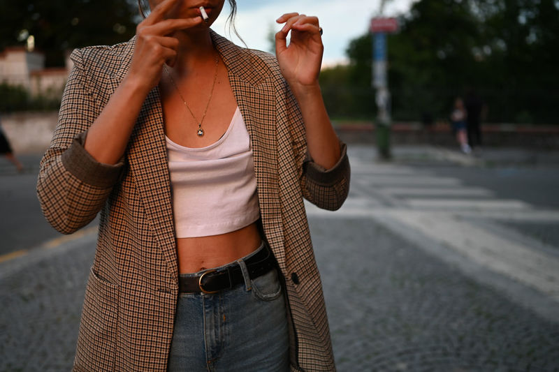 Midsection of woman smoking cigarette while standing outdoors