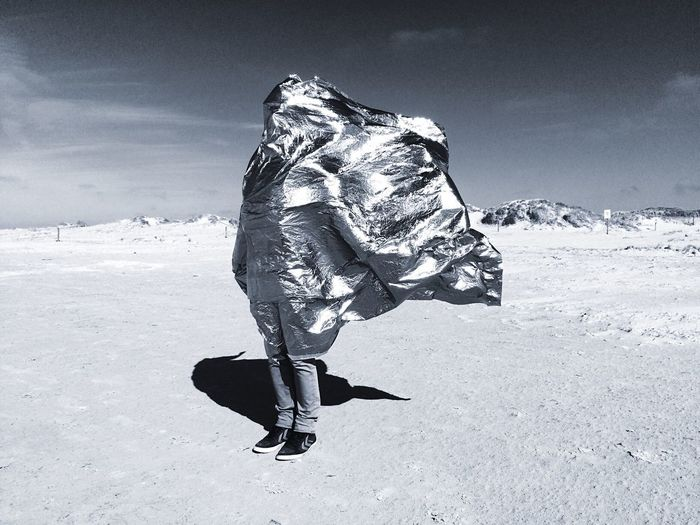 Man covered with silver fabric standing on barren field