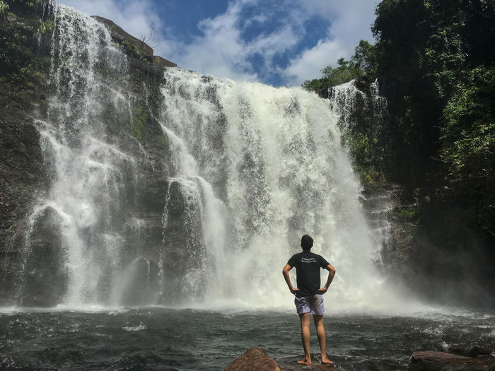 Rear view of man with hands on hip looking at waterfall