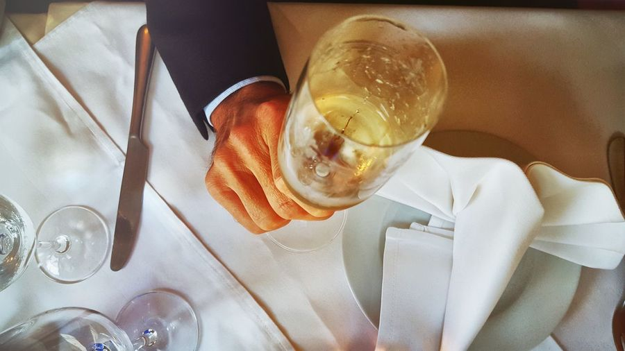 Cropped Image Of Businessman Holding Champagne Flute Over Dining Table In Restaurant