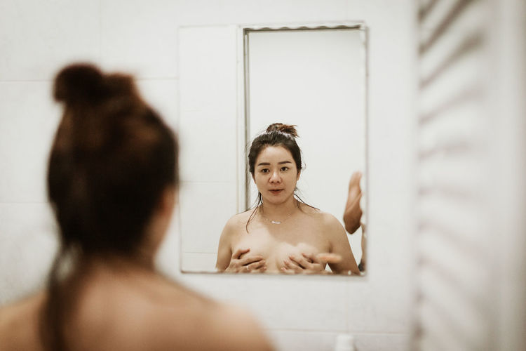 Portrait of woman holding breasts while looking in mirror
