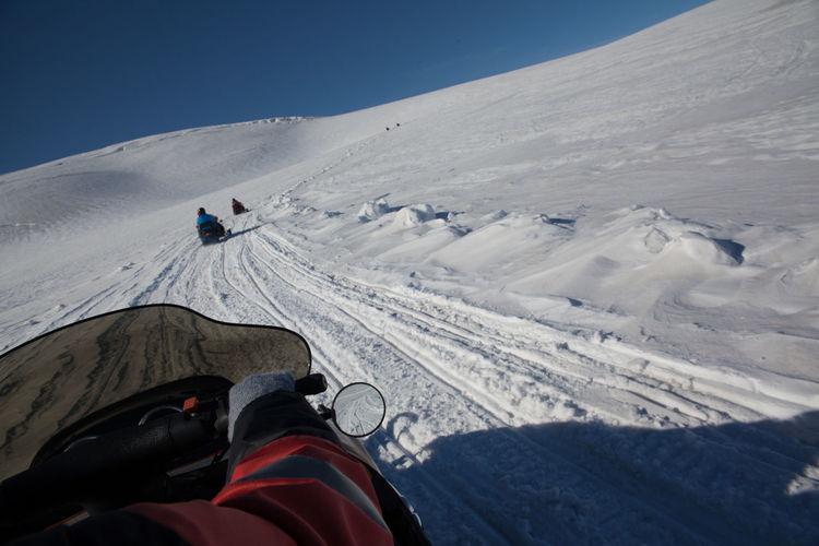 Tourist Riding Snowmobile On Snowy Field