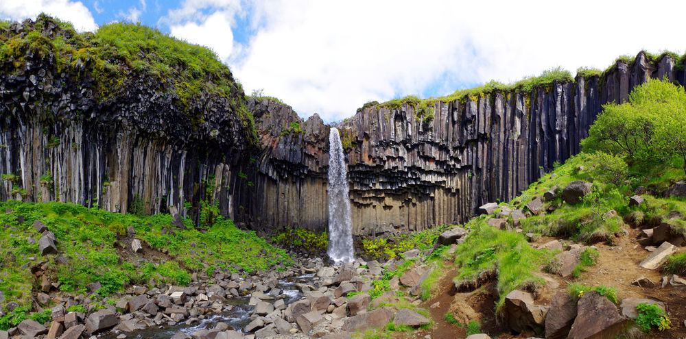 panorama of the beautiful svartifoss waterfall in iceland, which can be reached after a small hike uphill starting from the skaftafell national park visitor center! Basalt Basalt Columns Basalt Rock Blue Cloud - Sky Creek Day Grass Green Hiking Iceland Landscape Nature No People Outdoors River Rock Rock Formation Sky Stream Svartifoss Travel Destinations Tree Water Waterfall