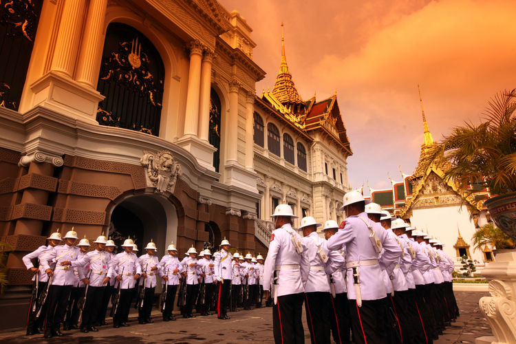 Army soldiers standing by historic building during sunset