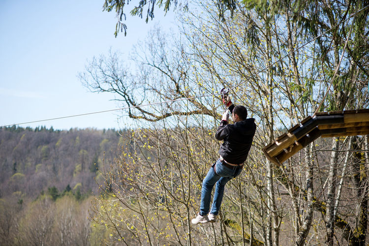 Man Hanging On Zip Line By Trees At Forest