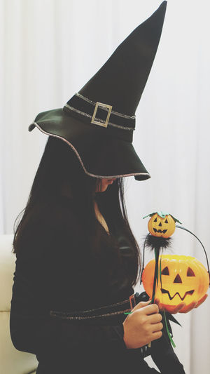 Midsection of person holding umbrella during halloween