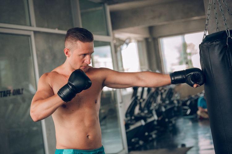 Shirtless boxer practicing boxing