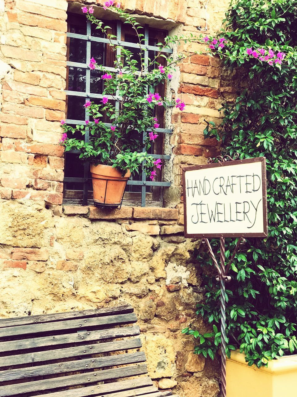 text, plant, communication, architecture, built structure, sign, potted plant, western script, no people, growth, flower, nature, flowering plant, building exterior, day, information, wall, outdoors, wall - building feature, information sign, flower pot, brick, window box, message