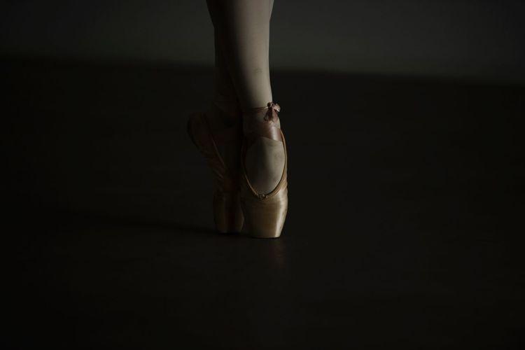 Low section of ballet dancer dancing on floor in darkroom