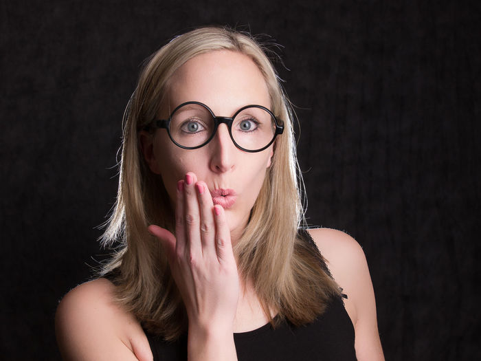 Portrait Front View Looking At Camera Young Adult One Person Headshot Blond Hair Young Women Black Background Hair Eyeglasses  Studio Shot Glasses Indoors  Women Cut Out Beautiful Woman Hand Beauty Hairstyle Hands Covering Mouth Surprised