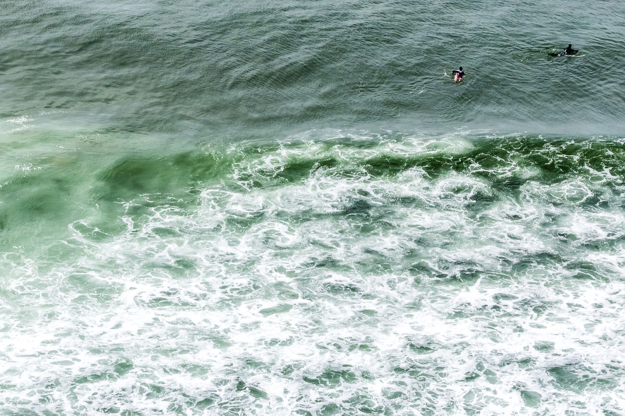 sea, sport, water, aquatic sport, surfing, wave, motion, day, nature, beauty in nature, waterfront, people, scenics - nature, unrecognizable person, high angle view, extreme sports, lifestyles, land, real people, outdoors, power in nature