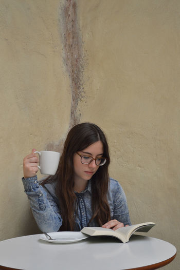 Young Woman Reading Book While Having Coffee At Table
