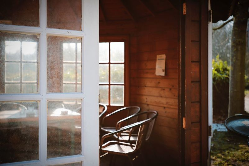 Country Living Wood Absence Architecture Ashtray  Built Structure Chair Country Style Day Indoors  Interior No People Open Door Selective Focus Smoking Area  Summer House Table Window Wood - Material Wood House Wooden House