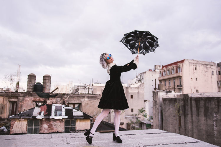 Low angle view of woman holding umbrella on terrace against sky