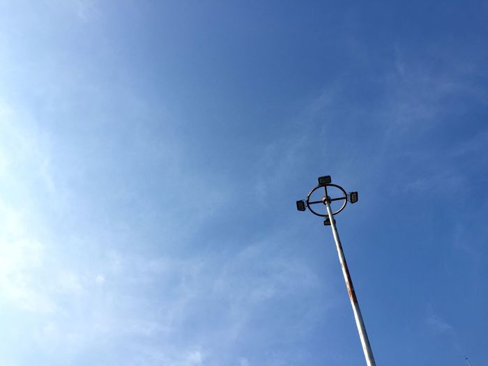 Low angle view of street light against blue sky
