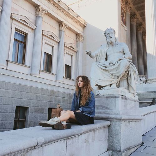 Full Length Of Beautiful Woman Sitting By Statue Against Historic Building